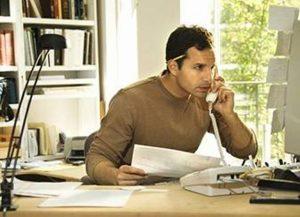 Как заработать в интернете реально. Мужчина за столом с телефоном